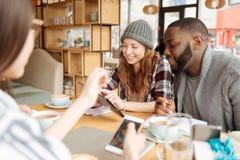 Étudiants de sourire positifs se reposant dans le café Photographie stock libre de droits