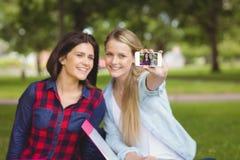 Étudiants de sourire prenant un selfie extérieur Photo libre de droits