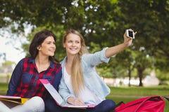 Étudiants de sourire prenant un selfie extérieur Image libre de droits