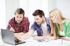 Étudiants de sourire regardant l'ordinateur portable l'école Images libres de droits