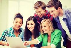 Étudiants de sourire regardant l'ordinateur portable l'école Photo stock
