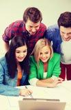 Étudiants de sourire regardant l'ordinateur portable l'école Image libre de droits