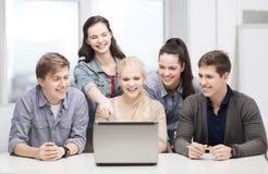 Étudiants de sourire regardant l'ordinateur portable l'école Photos stock