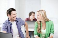 Étudiants de sourire regardant l'un l'autre l'école Photos stock