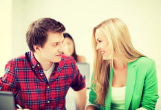 Étudiants de sourire regardant l'un l'autre l'école Image stock