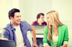 Étudiants de sourire regardant l'un l'autre l'école Photographie stock