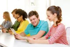 Étudiants de sourire regardant le PC de comprimé l'école Photographie stock libre de droits