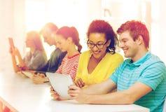 Étudiants de sourire regardant le PC de comprimé l'école Photo stock