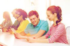 Étudiants de sourire regardant le PC de comprimé l'école Images libres de droits
