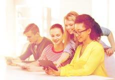 Étudiants de sourire regardant le PC de comprimé l'école Image libre de droits