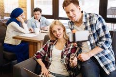Étudiants de sourire s'asseyant dans le café Images stock