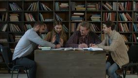 Étudiants de sourire se préparant aux examens dans la bibliothèque banque de vidéos