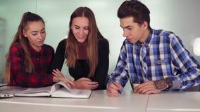 Étudiants de sourire travaillant à leur travail se reposant ensemble à la table et au café potable Groupe des jeunes dessus clips vidéos