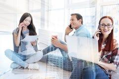 Étudiants de sourire travaillant et parlant au téléphone Image libre de droits