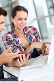 Étudiants des jeunes travaillant sur l'ordinateur portable Image libre de droits