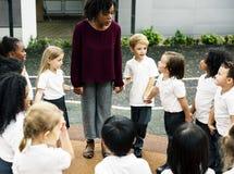 Étudiants divers de jardin d'enfants se tenant tenants des mains ensemble Photos stock