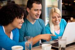 Étudiants en café avec l'ordinateur portable Image stock