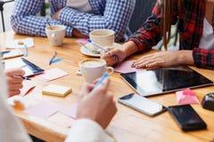 Étudiants en gros plan écrivant sur un fond de table Les gens travaillant avec des papiers et des dispositifs Concept de travail  Photographie stock libre de droits