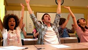 Étudiants enthousiastes encourageant dans la salle de classe banque de vidéos
