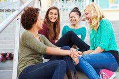 Étudiants féminins de lycée s'asseyant à l'extérieur du bâtiment Image stock