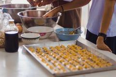 Étudiants faisant des biscuits de Singapour à partir de la pâte à l'école Photos stock