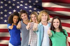 étudiants faisant des pouces sur le fond de drapeau américain Photos stock