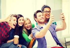 Étudiants faisant la photo avec le PC de comprimé à l'école Photo stock