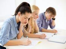 Étudiants fatigués avec des carnets à l'école Photos stock