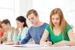 Étudiants fatigués avec des manuels et des livres à l'école Photo stock