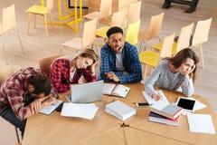Étudiants fatigués s'asseyant dans la bibliothèque Photos stock