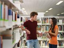Étudiants flirtant dans la bibliothèque images libres de droits