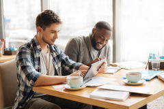 Étudiants futés agréables s'asseyant dans le café Photo stock