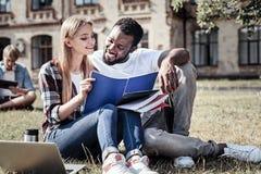 Étudiants futés joyeux lisant des notes de conférence Photographie stock libre de droits