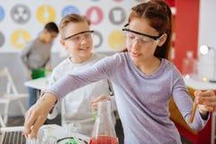 Étudiants gais étant occupés avec l'expérience chimique Photos stock