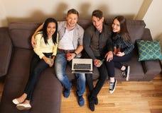 Étudiants gais avec l'ordinateur portable Photographie stock