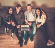 Étudiants gais avec l'ordinateur portable sur un sofa Photographie stock libre de droits