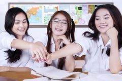 Étudiants gais de lycée joignant des mains Photo stock