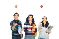 Étudiants gais jouant avec des pommes Images stock