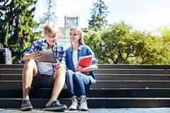 Étudiants gais s'asseyant dehors et travaillant au touchpad photographie stock