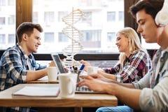 Étudiants gais s'asseyant ensemble dans le café Photos stock