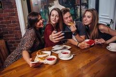 Étudiants gais traînant dans un café prenant la photo avec le téléphone tout en dînant ensemble Photo stock