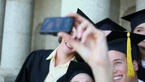 Étudiants gradués de sourire se photographiant banque de vidéos