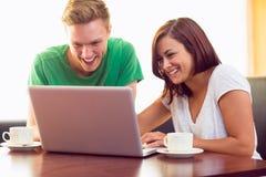 Étudiants heureux à l'aide de l'ordinateur portable tout en ayant le café au café photographie stock libre de droits