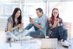Étudiants heureux à l'aide des téléphones portables Image libre de droits