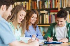 Étudiants heureux écrivant aux carnets dans la bibliothèque Photos libres de droits