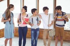 Étudiants heureux agissant l'un sur l'autre les uns avec les autres dans le couloir Images libres de droits