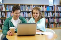 Étudiants heureux avec l'ordinateur portable dans la bibliothèque Image libre de droits