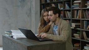 Étudiants heureux avec la mise en réseau d'ordinateur portable dans la bibliothèque banque de vidéos