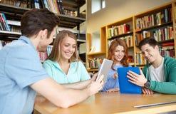 Étudiants heureux avec le PC de comprimé dans la bibliothèque Photos stock