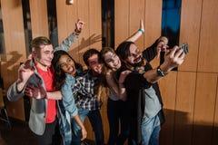Étudiants heureux ayant l'amusement et faisant le selfie se tenant prêt la fenêtre dans la grande salle Images stock